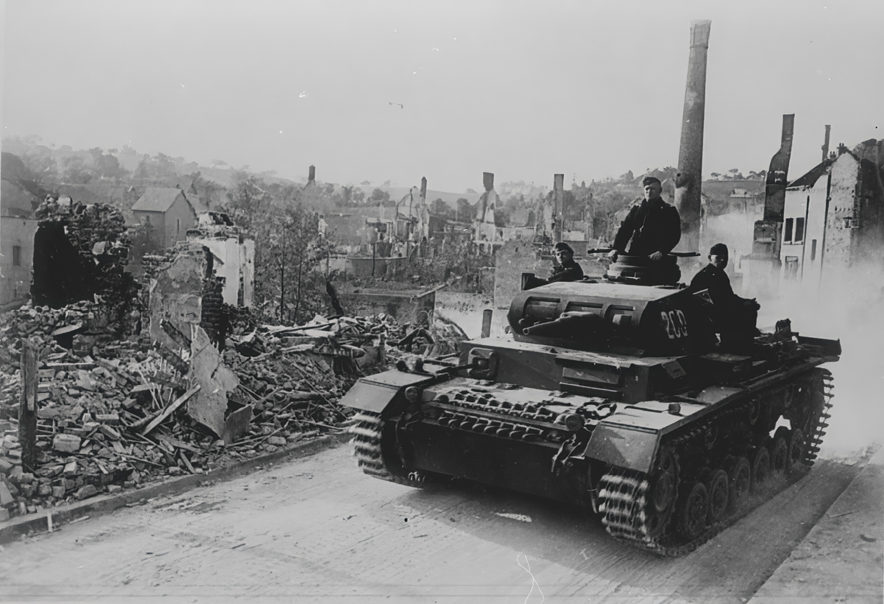 Wehrmacht Panzer III tanks drive through a bombed out town France 21st Jun 1940 NIOD