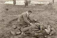 Asisbiz German atrocities Grief striken father cant beleive the sight of his murdered family by German soldiers 02