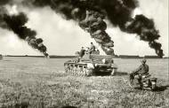 Asisbiz Panzer IV and motorcycle advance across a field and toward a smoke filled horizon 01