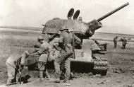 Asisbiz Soviet T 34 tank abandoned is being salvaged by Soviet prisoners during a clean up by German forces 01