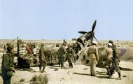 Asisbiz German and Italian troops inspect a burnt out Hurricane wreck Western Desert 01