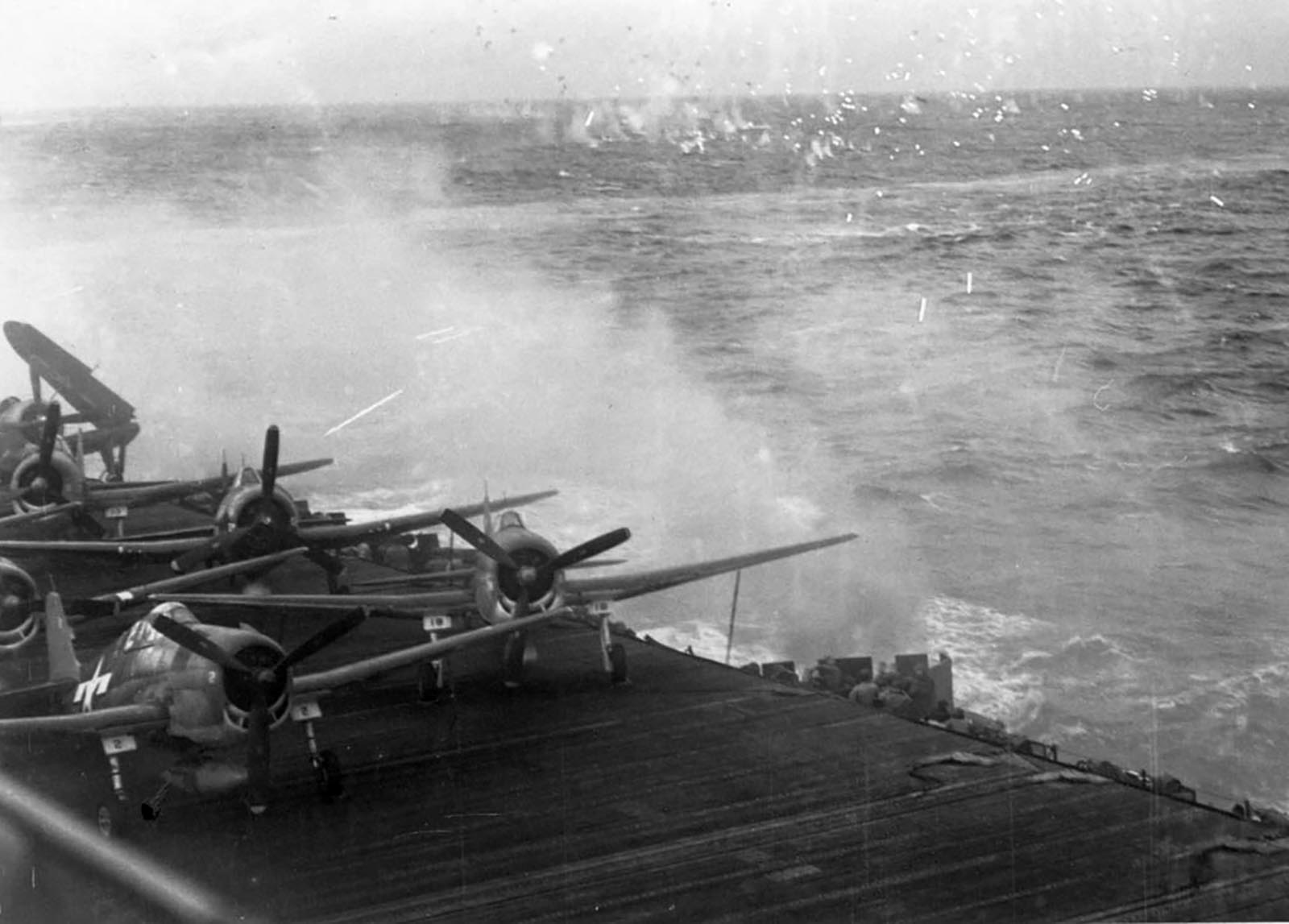 Grumman F6F 5 Hellcats VF 19 lay exposed on deck as CV 16 comes under attack Nov 1944 01