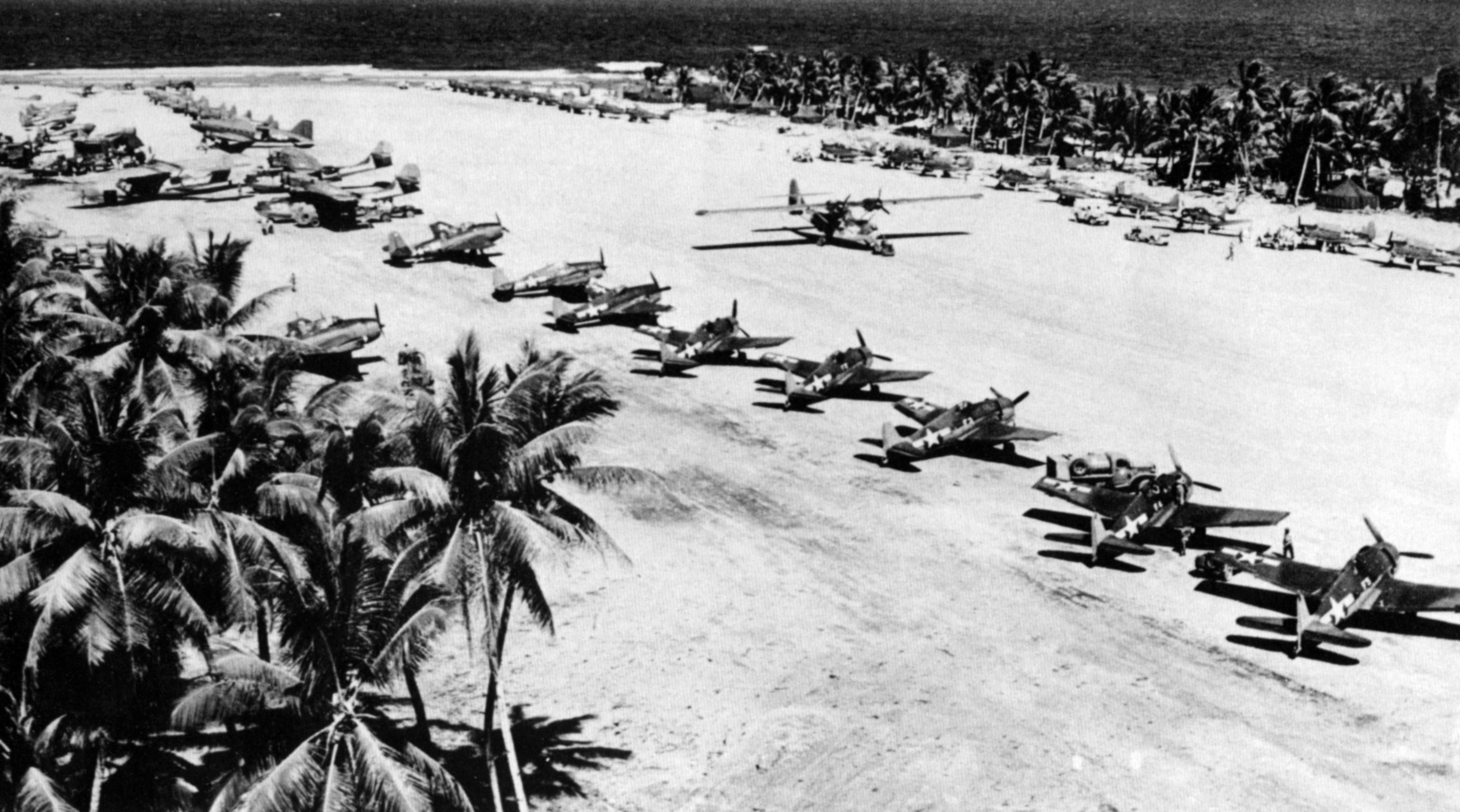 Large photo of a Tropical airstrip showing amongst other things a squadron of parked Hellcats 01