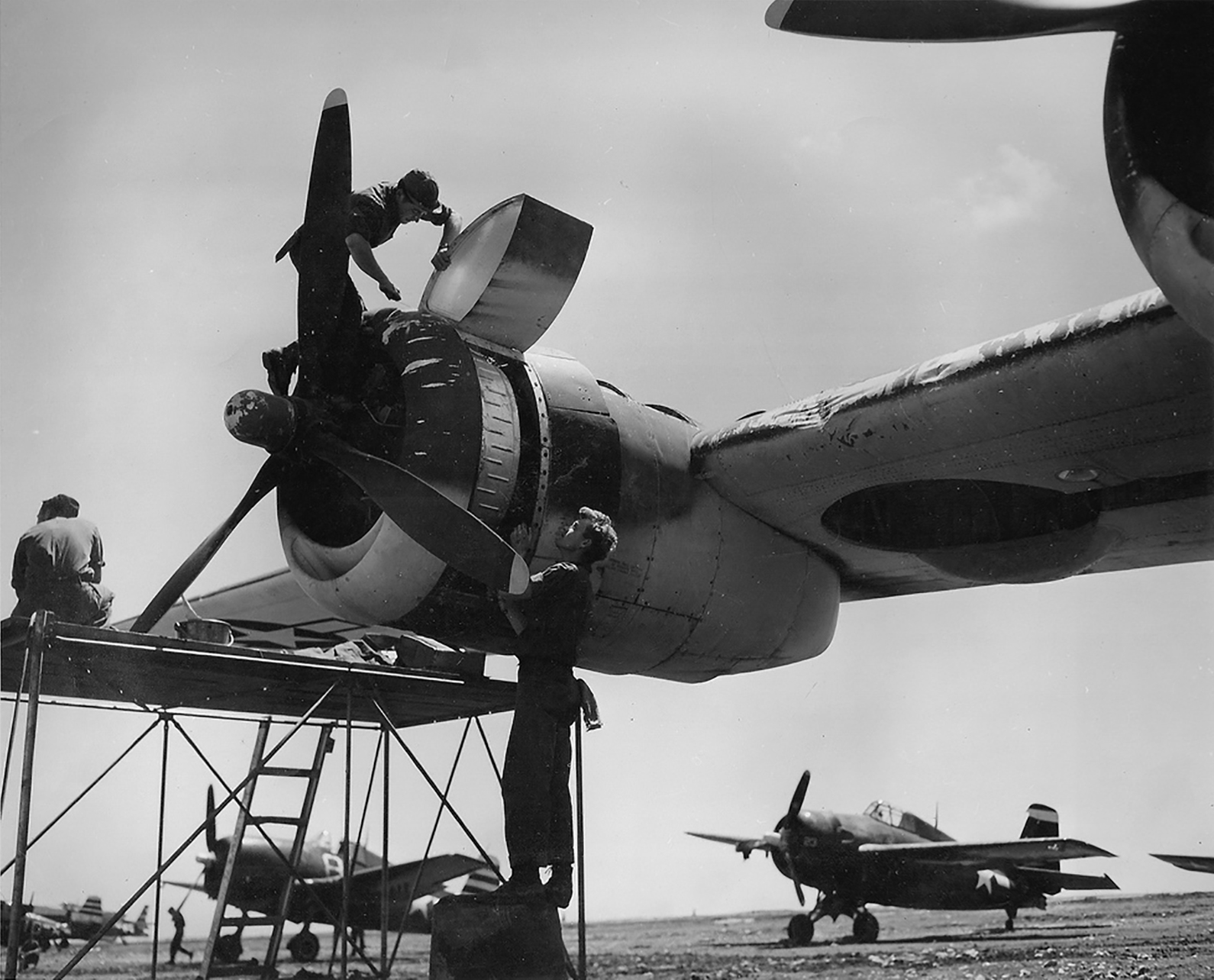 Grumman F6F 5 Hellcat VF 12 White 8 with a Wildcat and PB4Y 1 at a USN maintenance base 01