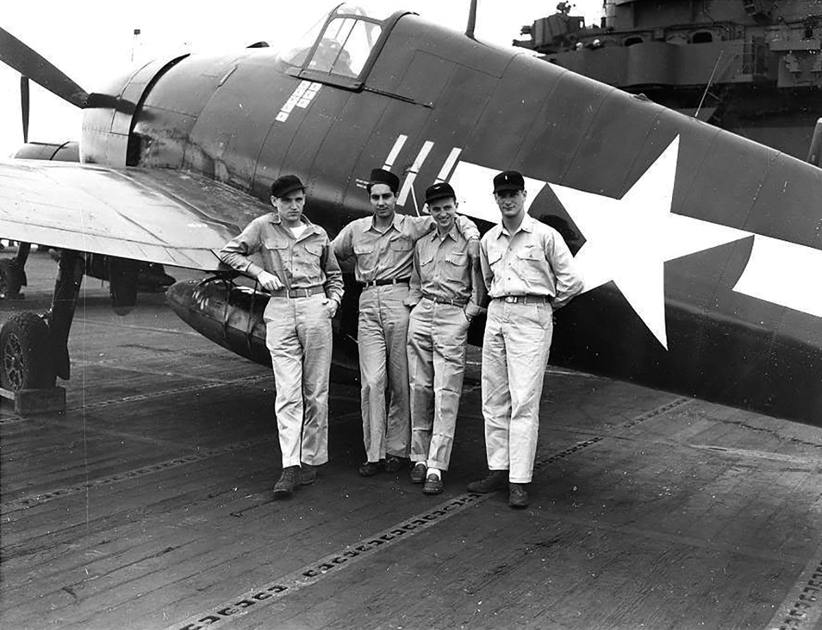 Aircrew USN personnel pose next to F6F 5 Hellcat White 111 belonging to VF 83 ace LtCdr Thaddeus T Coleman 01