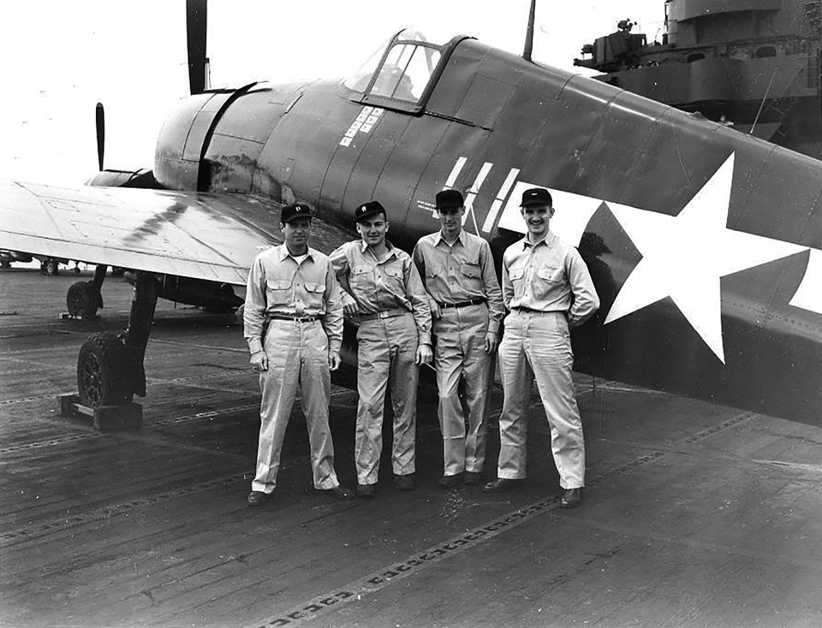 Aircrew USN personnel pose next to F6F 5 Hellcat White 111 belonging to VF 83 ace LtCdr Thaddeus T Coleman 02