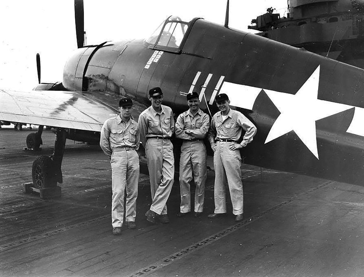 Aircrew USN personnel pose next to F6F 5 Hellcat White 111 belonging to VF 83 ace LtCdr Thaddeus T Coleman 03