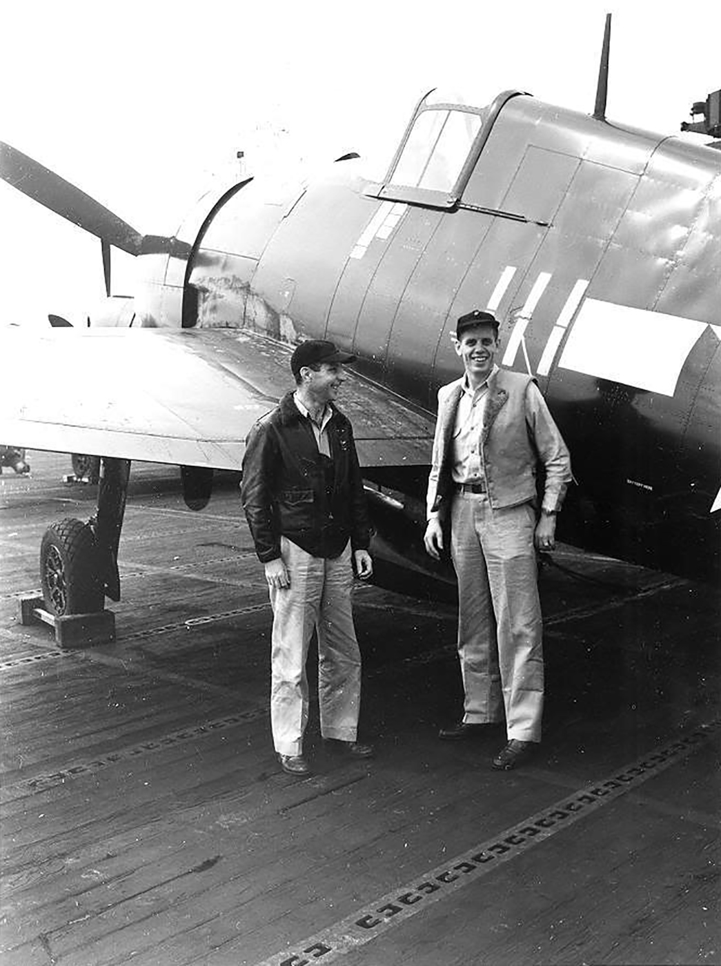 Aircrew USN personnel pose next to F6F 5 Hellcat White 111 belonging to VF 83 ace LtCdr Thaddeus T Coleman 04