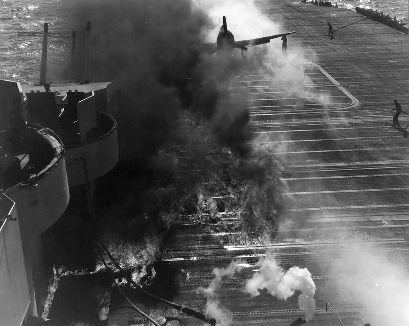 Fire engulfs the USS Essex flight deck after a Hellcats drop tank burst on landing 16 Dec 1944 02