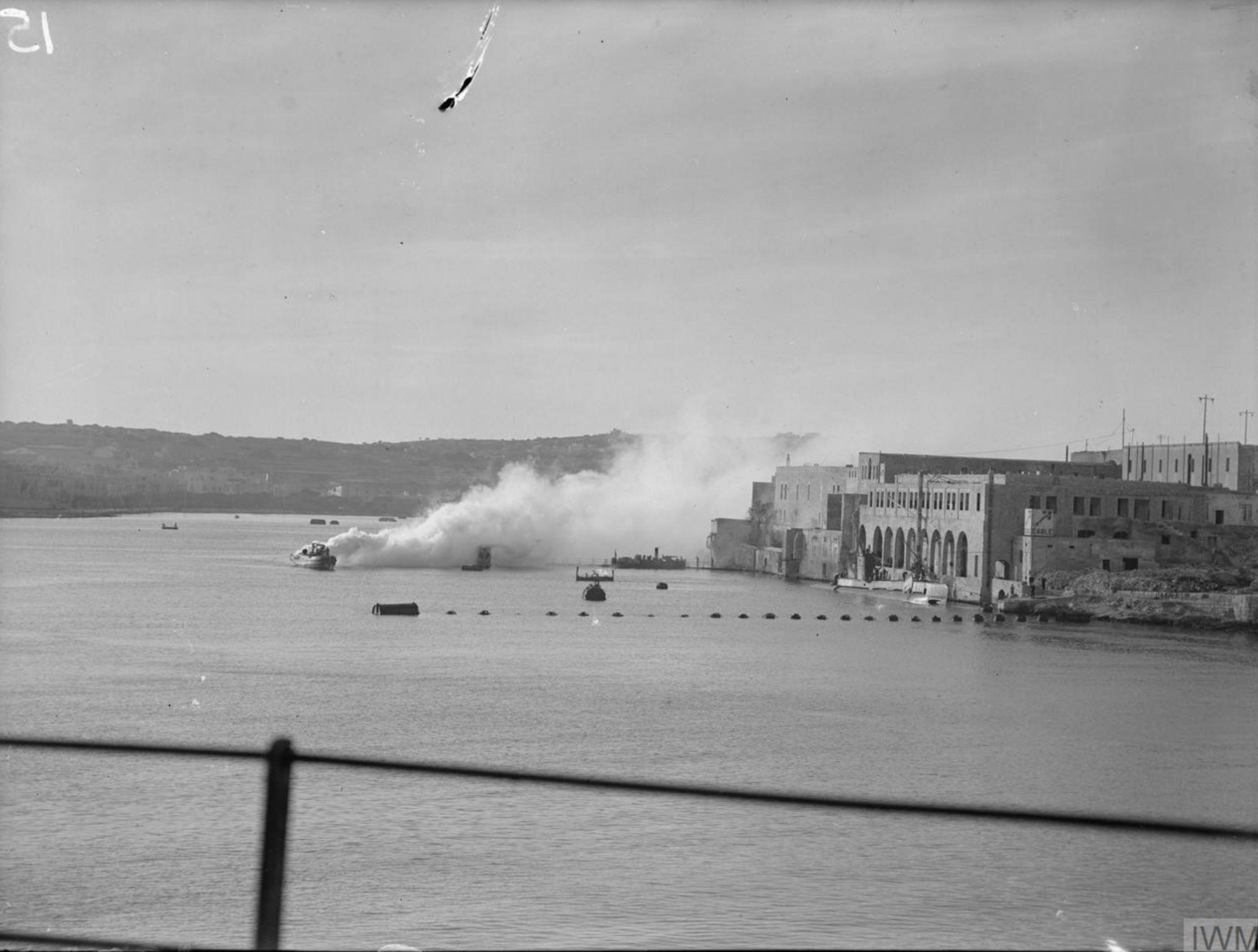 Harbour craft making a smoke screen at HMS Talbot the Royal Naval Submarine Base at Malta IWM A14392