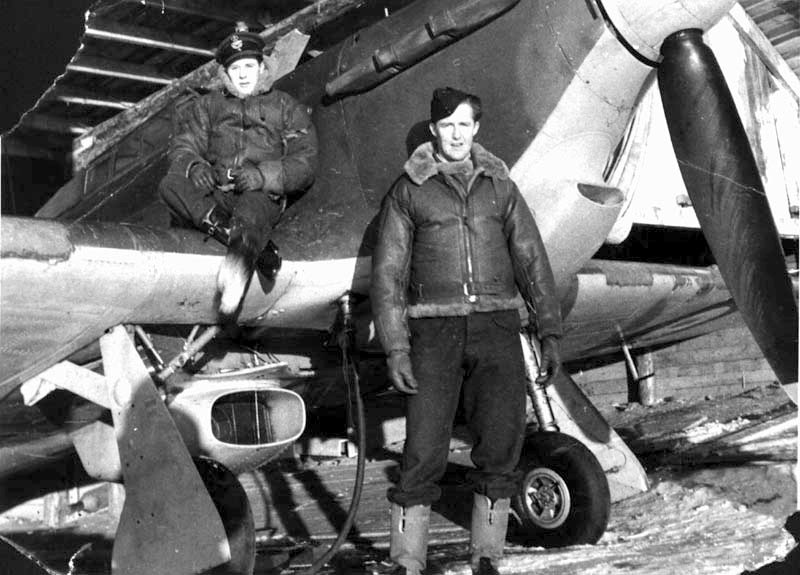 Aircrew RAF PltOff Edmiston on wing and PltOff Sheldon standing with a Hurricane in one of the hangers 01