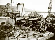 Asisbiz Reinforcing Crete scene on the quayside as the warship was disembarking men and material IWM E1158