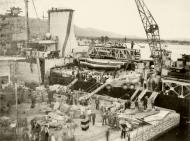 Asisbiz Reinforcing Crete scene on the quayside as the warship was disembarking men and material IWM E1159