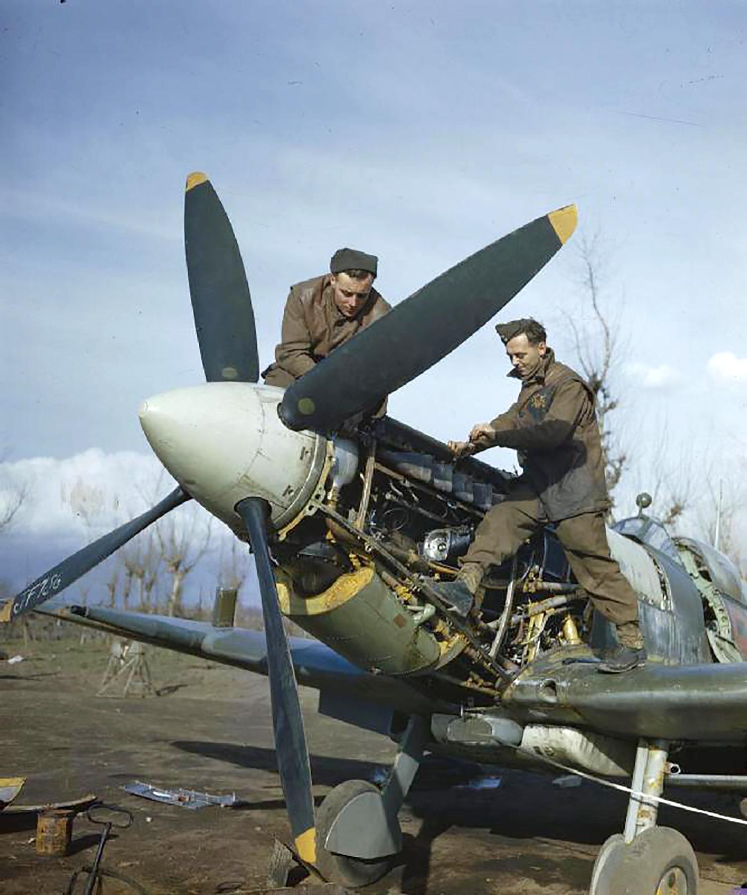 Spitfire MkIX RAF 241Sqn ground crew Jim Birkett Wally Passmore working on a Merlin engine IWM 01