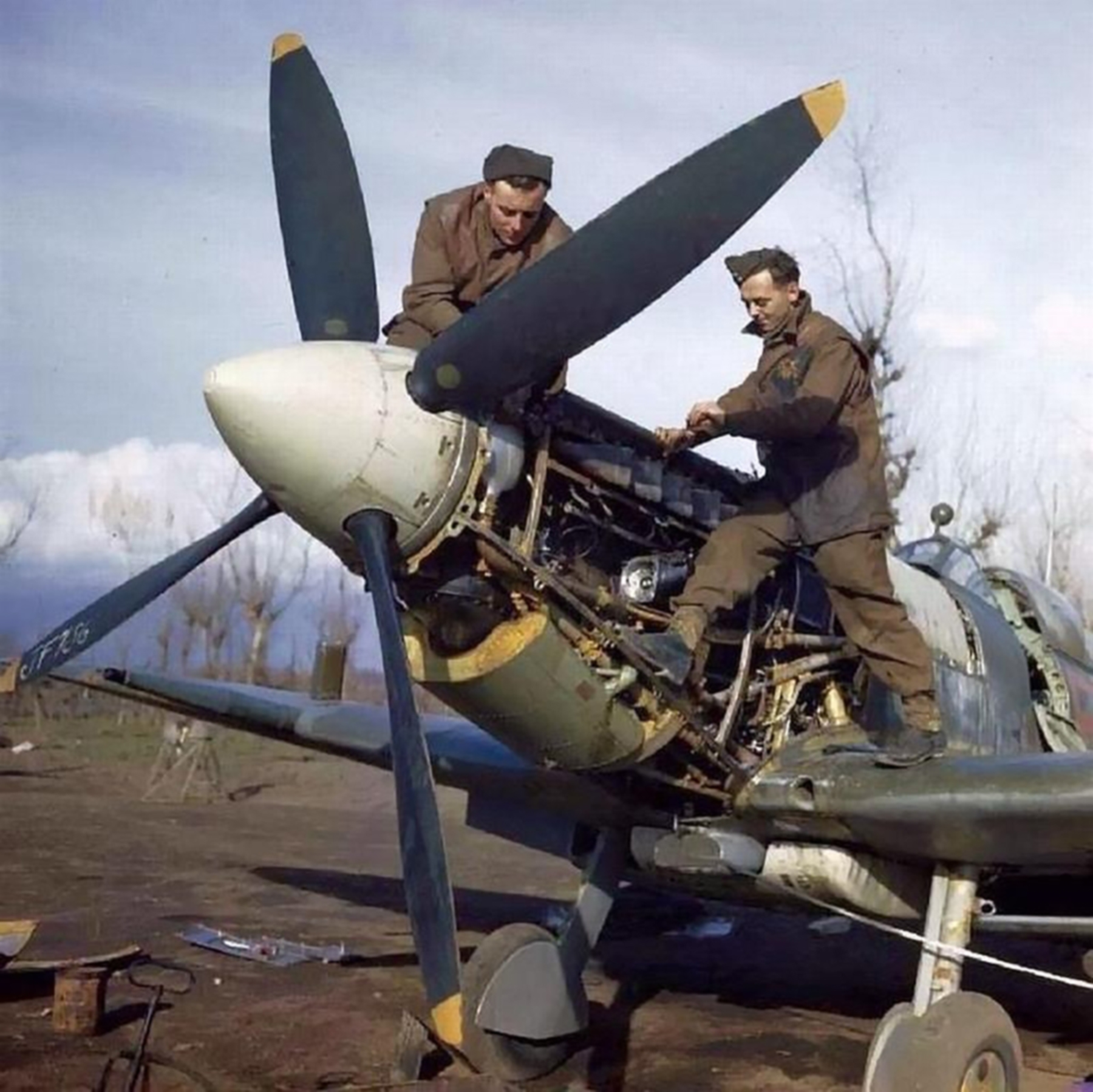 Spitfire MkIX RAF 241Sqn ground crew Jim Birkett Wally Passmore working on a Merlin engine IWM 02