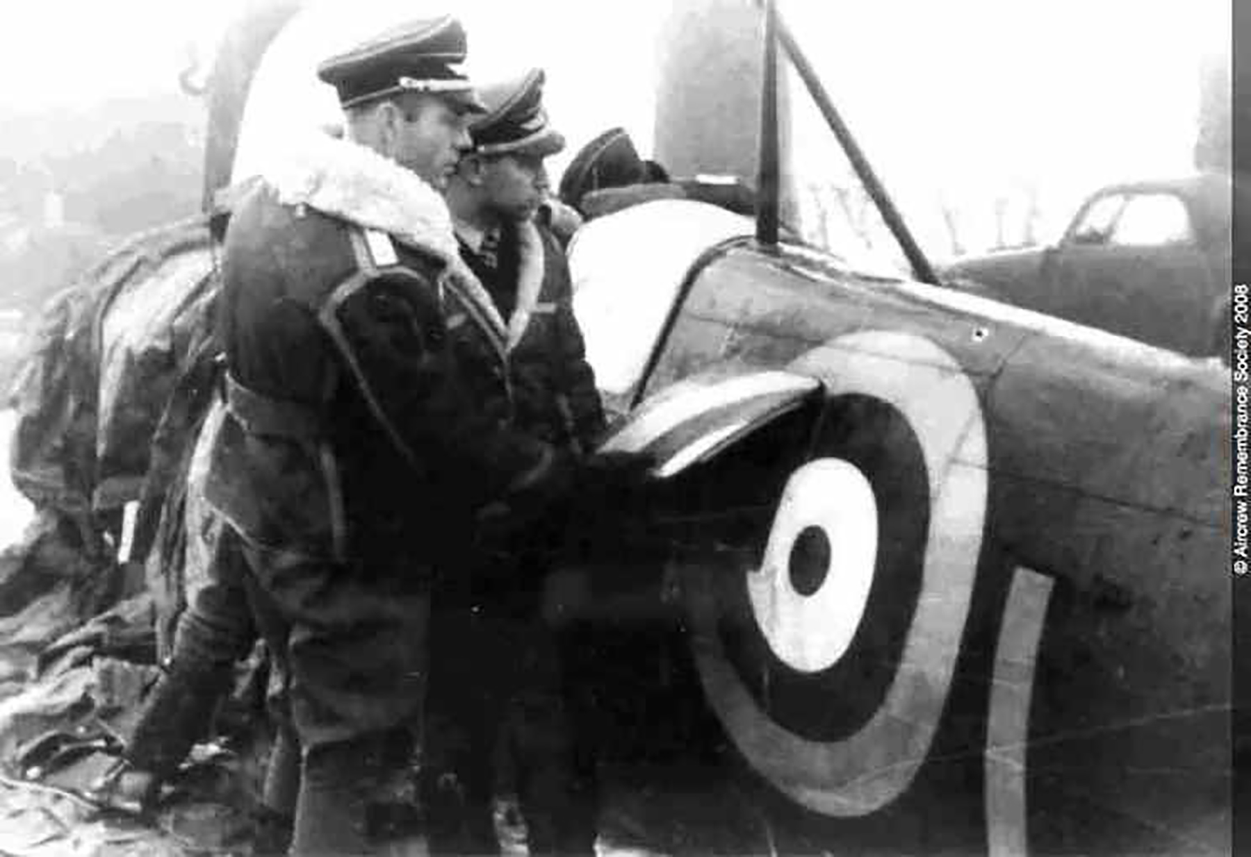 Aircrew Luftwaffe pilots looking over the wreck of P7665 YTL left side 01
