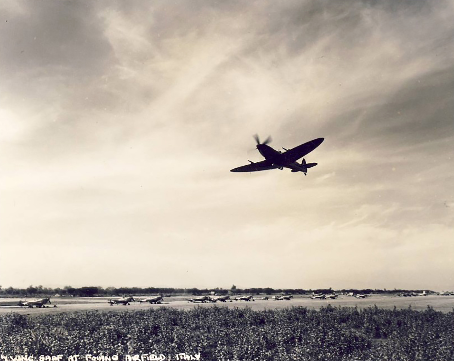 Spitfire MkVII c wing taking off at a base in Italy 01